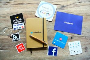 Table with pieces of paper displaying different online social media icons
