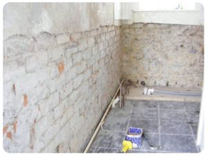 Wall with plaster pealed off as specialists deal with rising damp