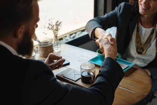 Man and woman shake hands in business meeting for success
