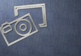 Silver Stitched Camera Logo on Blue Material