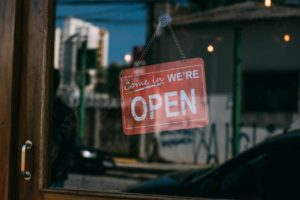 Red Open Sign hung on glass door of small business