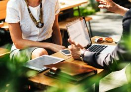 Man and woman conducting a small business meeting at an outdoor cafe